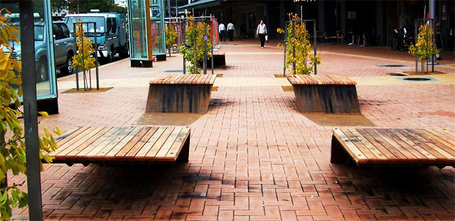 &quot;Wellington's ubiquitous terracotta tiling is out in full force. This, more than anything, enables the park to act as an extension of the footpath. While this is certainly in-line with the park's goals – would a greater variety in the ground plane be too much to ask? Even a minor substitution of the secondary tan brick would go a long way to creating more of a unique sense of place. <br><br> ...Sleek and simple in their elongated S-shape, the seat/bench hybrids echo the rustic materiality that has populated the waterfront. Since their Ghuznee debut, they have gained a softer timber seat-cover, as well as map-etchings and swiss-cheese punctures that add character to the design. I have to admit though, my first reaction to the design was: wait, can I stand on these things?&quot;